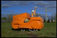 The robot, Nimby, is made of an electric wheelchair, a Netwinder computer, a GPS system, an ethernet line and a chalk talc dispenser. The shell was created out of vacuum formed ABS plastic and recalls the shape of a rider lawnmower.